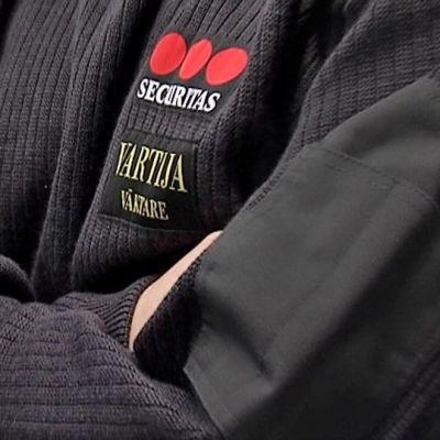 Securitaksen vartija seisoo vartiossa, kädet puuskassa, elintarvikekaupassa.