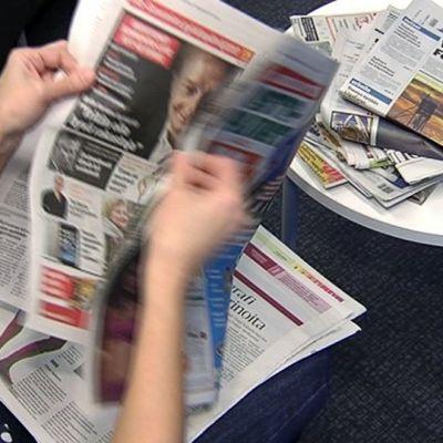 Henkilö lukemassa sanomalehtiä.