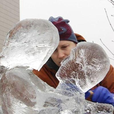 Mies veistää jääpatsasta.