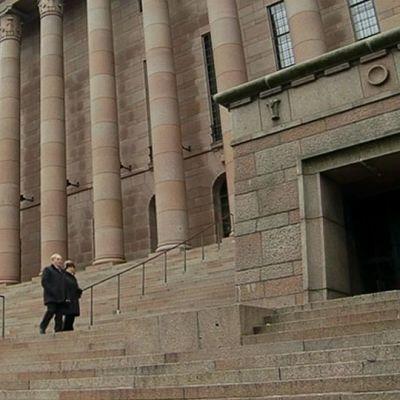 Ihmisiä kävelemässä Eduskuntatalon portailla.