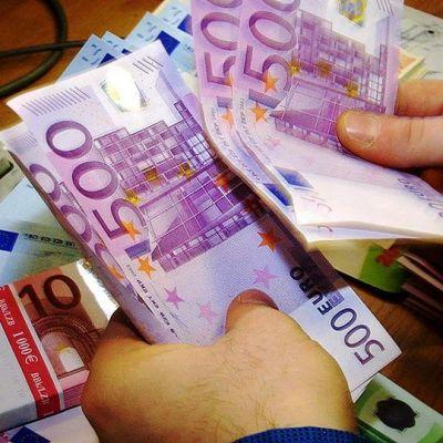 Henkilö laskemassa seteleitä.