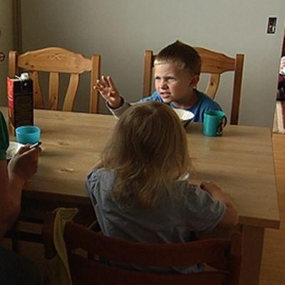 Äiti ruokailee kahden alle 6-vuotiaan lapsensa kanssa keittiössä.