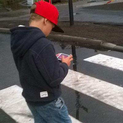 Lapsi tuijottaa kännykkäänsä suojatiellä