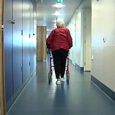 Vanhus kävelee roollattorin kanssa käytävässä.