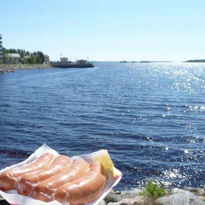 Makkarapaketti meren rannassa. Juhannusaiheinen kuva.