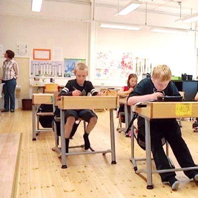Alakoulun lapset istuvat pulpeteissa.