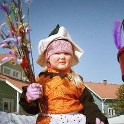 Pääsiäisnoidaksi pukeutunut lapsi kantaa virpomisvitsoja.