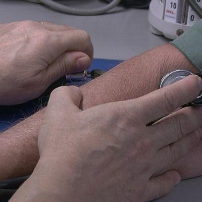 Terveyskeskuslääkäri Outi Seppälä mittaa potilaan verenpainetta.