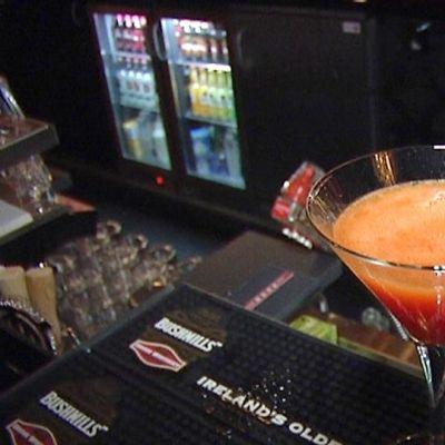 Kuvassa oranssi drinkki baaritiskillä