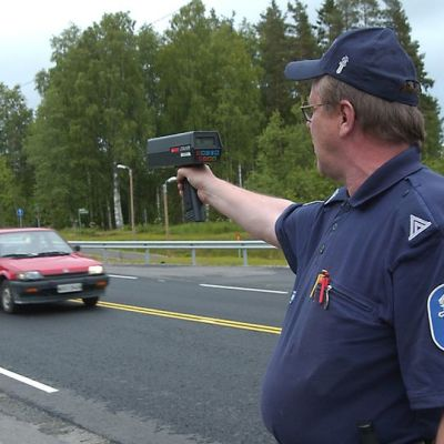 Poliisi tutka kädessä mittaamassa auton ajonopeutta