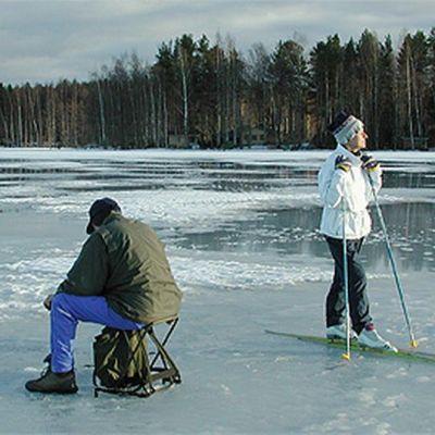 Pilkkijä ja hiihtäjä järven jäällä