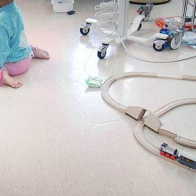 Lapsi leikkii lastensairaalan lattialla.