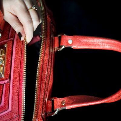 Nainen tunnustelee käsilaukkua.