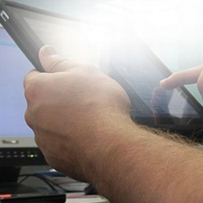 iPad-tietokone käsissä