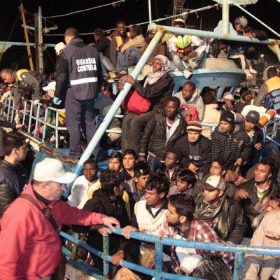 Täyteenlastattu pakolaisvene saapuu Lampedusan satamaan.