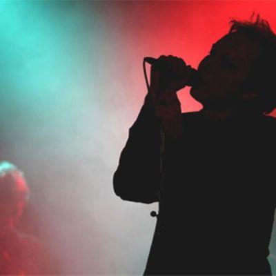 Laulajan silhuetti lavan punaisissa ja vihreissä valoissa.