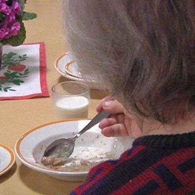 Vanhus syö puuroa.
