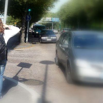Nainen seisoo jalkakäytävällä kädet korvillaan