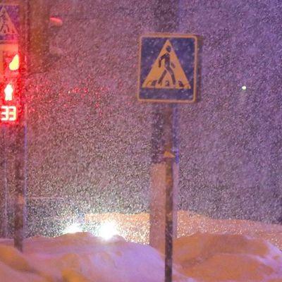 Jalankulkija seisoo liikennevaloissa Moskovassa sankassa lumisateessa.