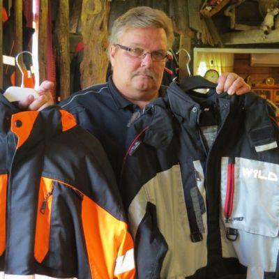 Torniolainen Wild Lapland Productsin yrittäjä Harri Muhonen kannattelee yrityksensä tuotteita, talvikäyttöön soveltuvaa työtakkia ja kelkkahaalaria.