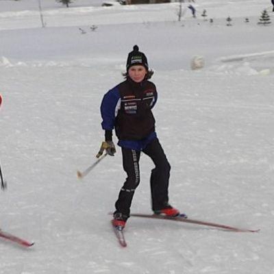 Kaksi tyttöä hiihtää.