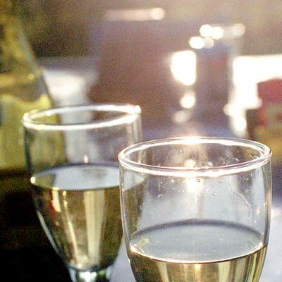 Valkoviinilaseja ja viinipullo pöydällä ulkona puutarhassa.