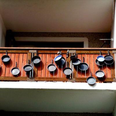 Paistinpannuja kiinnitettynä kerrostalon parvekkeeseen.