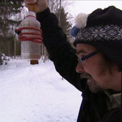 Pastori Antti Lankinen ottaa vesinäytettä.