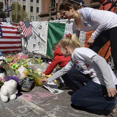 Ihmiset tuovat kukkia ja muita muistoesineitä lähelle Bostonin maratonin maaliviivaa.