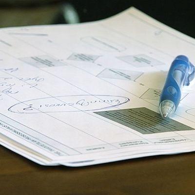Kynä ja muistiinpanoja pöydällä.