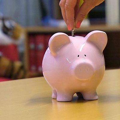 Henkilö laittaa kolikoita säästöpossuun.