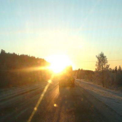 Talvinen auringonpaiste häikäisee auton tuulilasin. Edellä ajaa tyhjä rekka-auto nelostiellä.