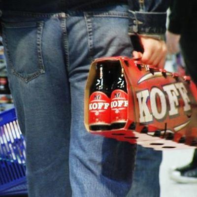 Mies kantaa olutpakkausta ruokakaupassa.