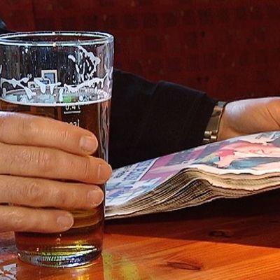 Mies juo olutta baarissa.