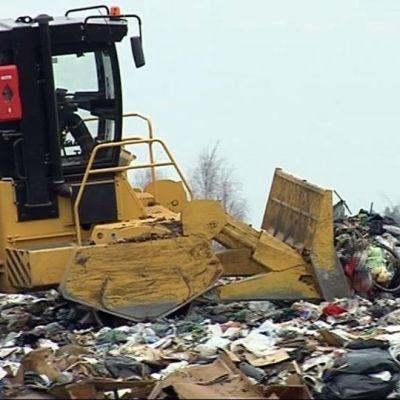 Kone työntää jätteitä kauhalla