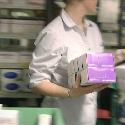 Apteekin työntekijä kulkee hyllyjen välissä lääkkeitä käsissään.