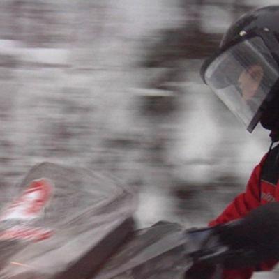 Moottorikelkka ajaa lumisessa metsässä.