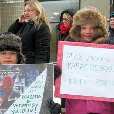 Lapset kantavat mielenosoituskylttejä
