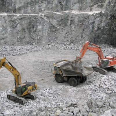 Talkkikaivos, jonka pohjalla kaksi kaivuria ja kuorma-auto.