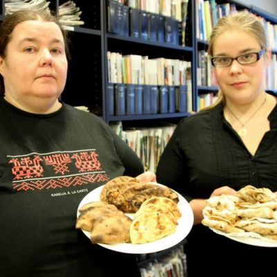 Naisilla käsissään lautaset, joilla pohjoiskarjalaisia leivonnaisia.