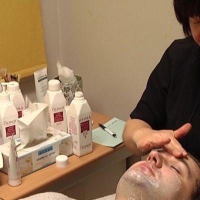 Kosmetologi Leena Paulus hoitaa Tapani Siivolan ihoa.