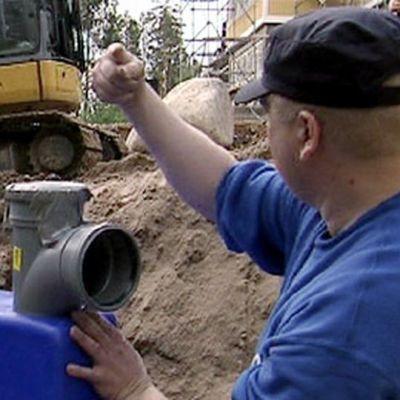 Jätevesien puhdisjärjestelmän asentaminen käynnissaä. Kaivinkone ja apumies.