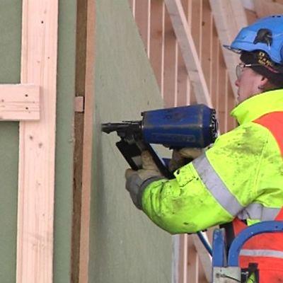 Rakennusmies kiinnittää eristelevyä rakennuksen seinään.