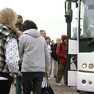 Ihmisiä nousemassa bussiin.