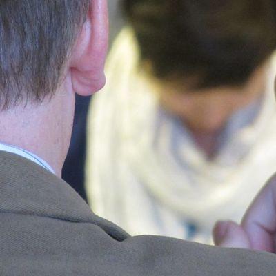 Mies heristää sormea kuvan taustalla olevalle henkilölle.