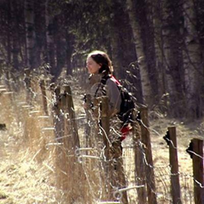 Nainen tarkkailee kevään merkkejä pellon laidalla.
