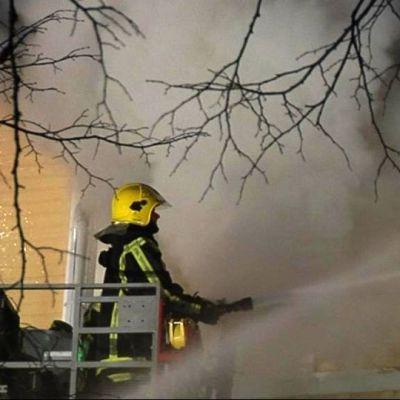 Palomies ruiskuttaa vettä rakennukseen ikkunoista.