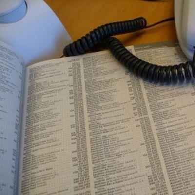 Aukinainen puhelinluettelo ja lankapuhelin pöydällä.