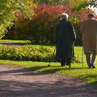 Kaksi vanhusta sauvakävelyllä