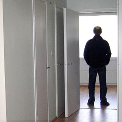 Mies seisoo tyhjässä asunnossa.